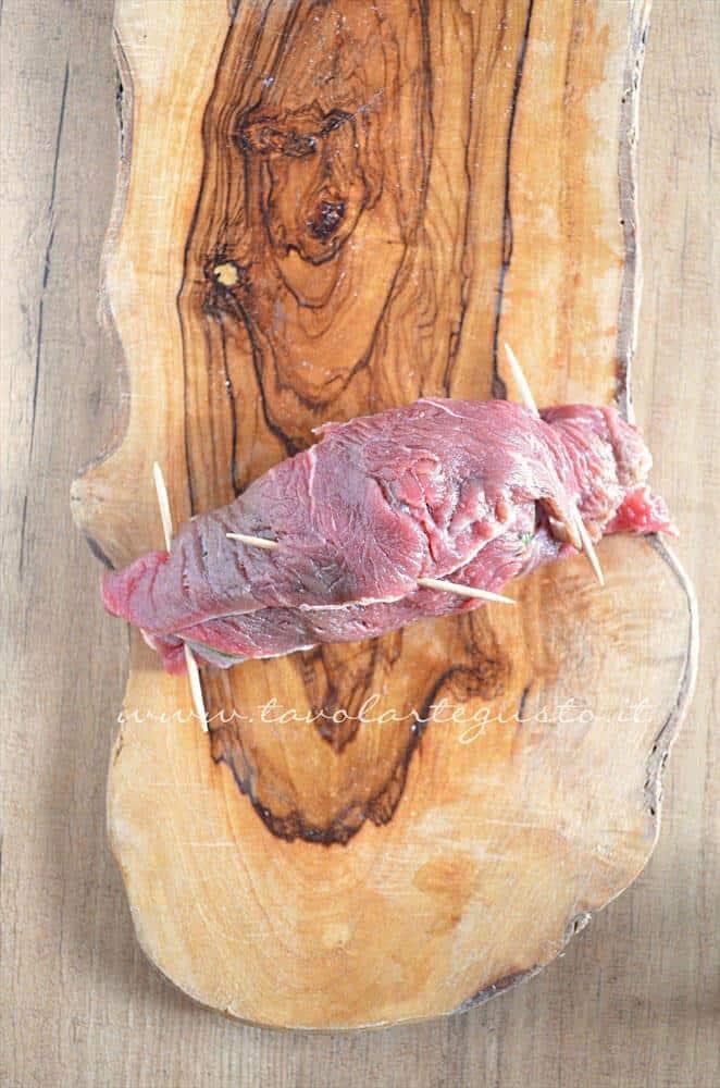 Chiudere l'involtino con l'aiuto di uno stuzzicadenti - Ricetta Involtini di carne con bietola e scamorza