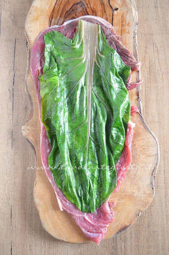 Disporre una foglia di bietola sulla fettina - Ricetta Involtini di carne con bietola e scamorza
