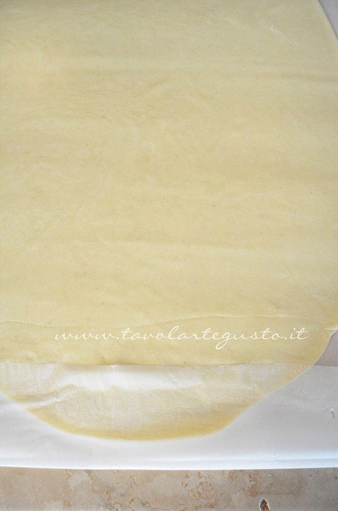 Ripiegare la carta da forno sulla sfoglia di Pasta Brisee - Ricetta Pasta Brisee
