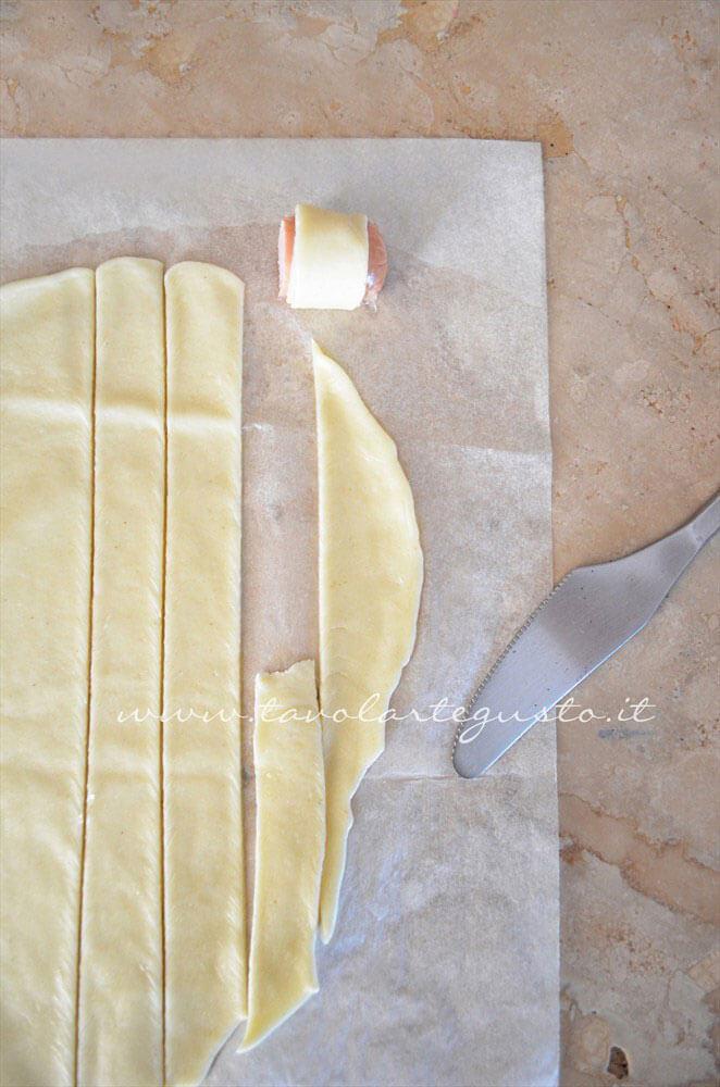 Avvolgere ogni pezzetto in una striscia di pasta brisee - Ricetta Rotolini di Wurstel in brisee