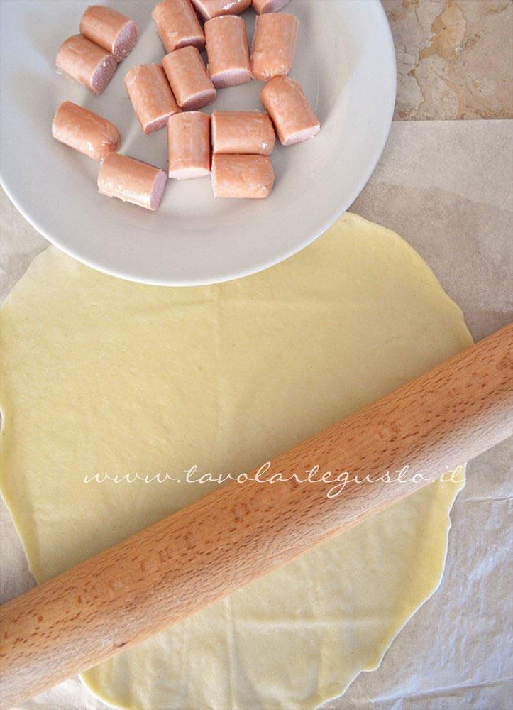 Tagliare a pezzetti i wurstel - Ricetta Rotolini di Wurstel in brisee
