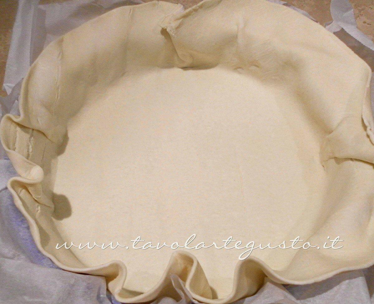 Adagiare la pasta sfoglia nella tortiera - Ricetta Torta salata con Carciofi