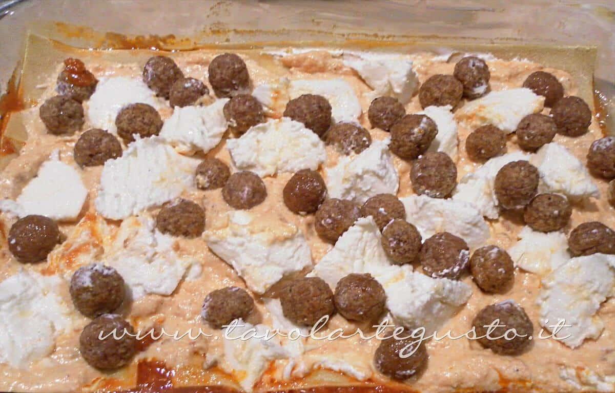 Adagiare uno strato di ricotta, mozzarella e polpettine - Ricette Lasagne napoletane