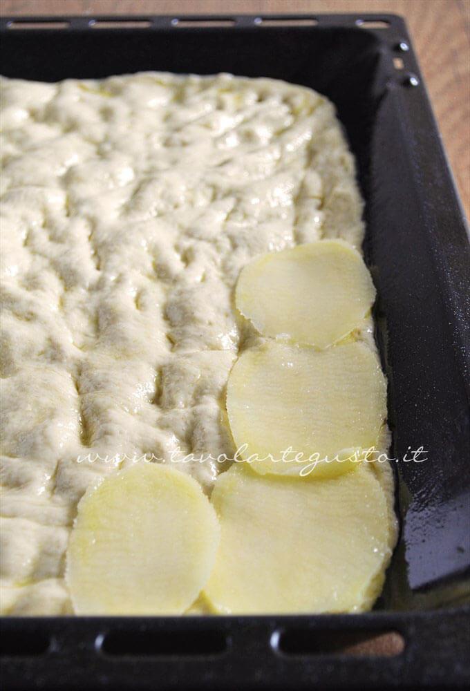 Adagiare sulla pizza le patate tagliate sottili - Ricetta Pizza con patate e rosmarino