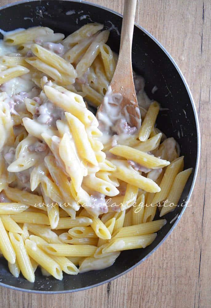 Unire la pasta alla besciamella e salsiccia  - Ricetta Pasta al forno besciamella e salsiccia