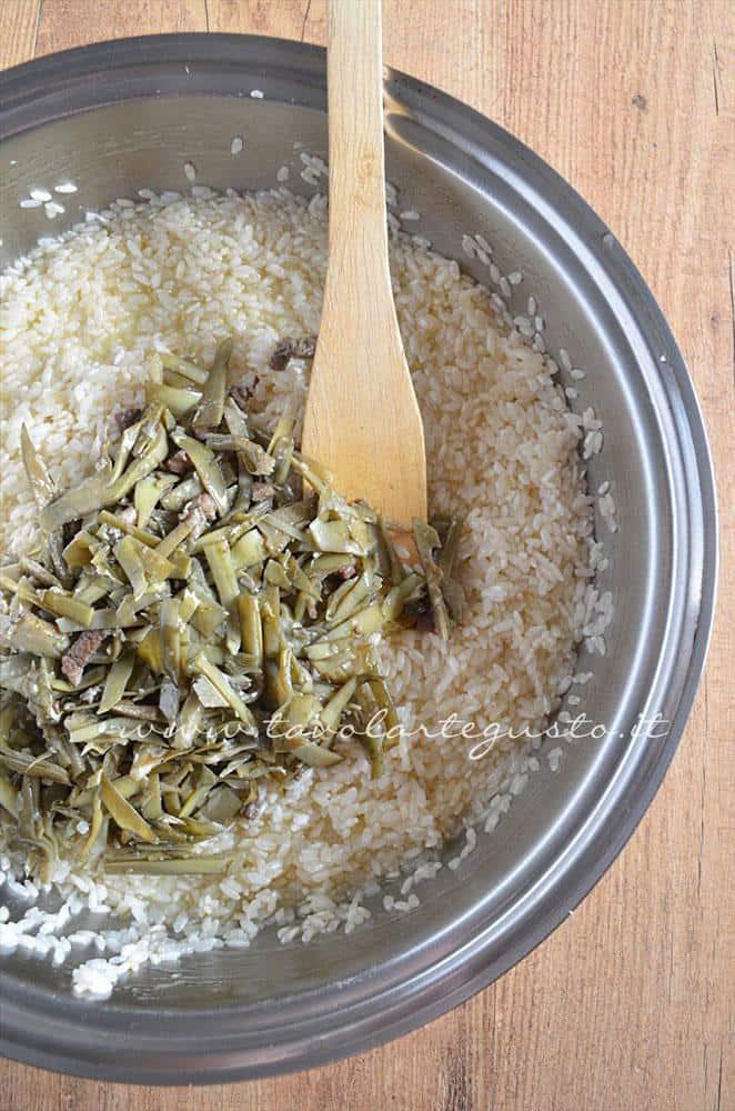Aggiungere i carciofi al riso - Ricetta Bordura di riso con crema di carciofi e crostini di Fiore Sardo