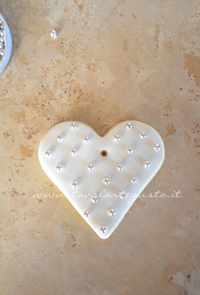 Completare realizzando una serie di pois obliqui su cui adagiare le perle di zucchero - Ricetta Biscotti di Natale decorati in Pasta di Zucchero