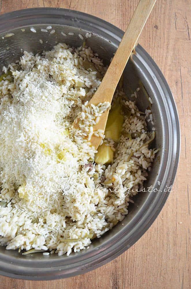 Mantecare il riso con olio, burro e formaggio - Ricetta Bordura di riso con crema di carciofi e crostini di Fiore Sardo