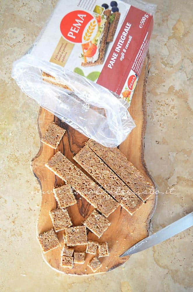Tagliare a pezzettini le fette di pane per realizzare i crostini - Ricetta Vellutata di cavolfiore