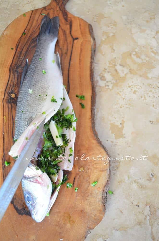 Aggiungere gli aromi nella pancia del Branzino - Ricetta Branzino al sale