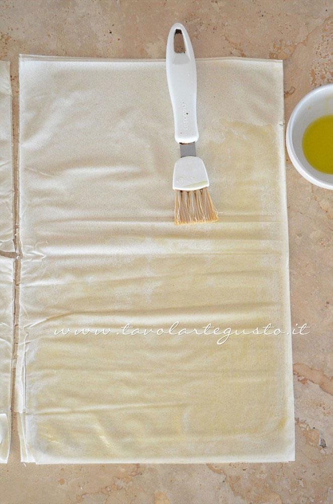 Pennellare la pasta fillo con olio extravergine - Ricetta Fagottini di pasta fillo con funghi e prosciutto