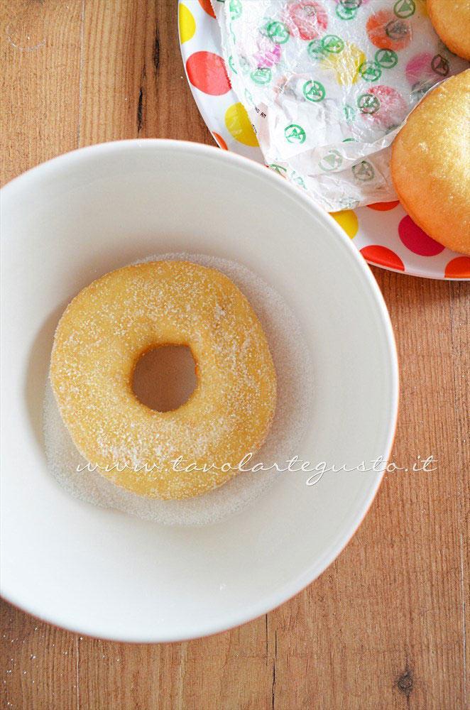 Rotolare le graffe nello zucchero una per volta - Ricetta Graffe senza patate