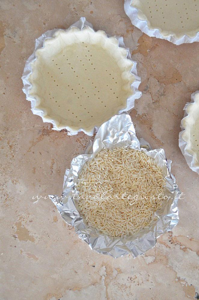 Inserire la pasta sfoglia negli stampi e preparare per la cottura in bianco - Ricetta Crostatine di pasta sfoglia alle due creme e frutti rossi