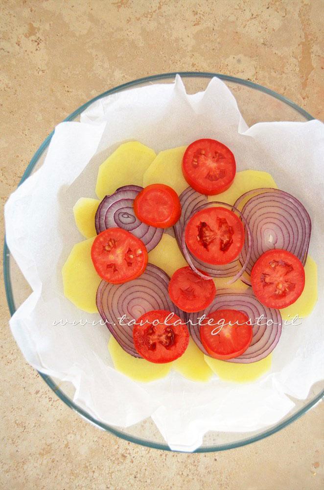 Disporre in tortiera il primo strato di verdure -Ricetta Patate e cipolle al forno con pomodori e pecorino