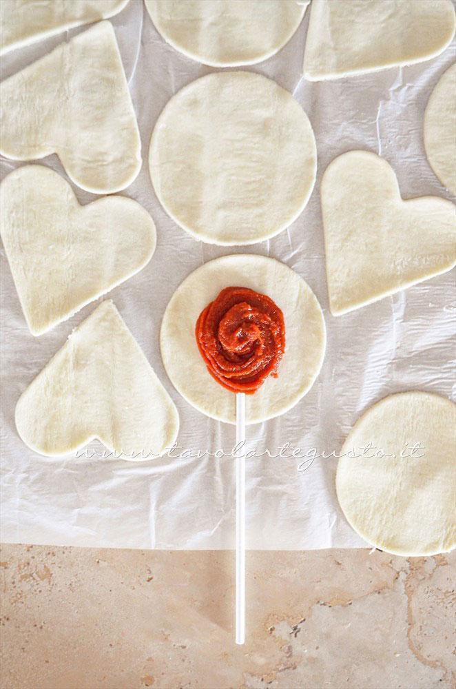 Inserire lo stecco sulla sfoglia farcita - Ricetta Lecca lecca salati di pasta sfoglia