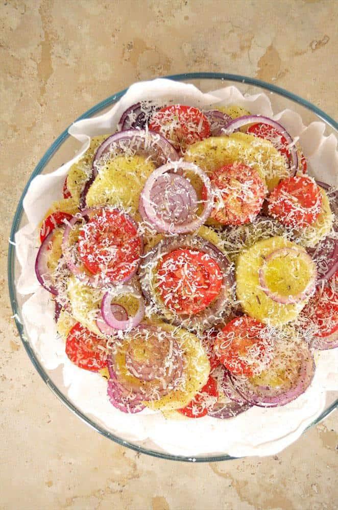 La teglia di Patate e cipolle pronta per essere infornata Ricetta Patate e cipolle al forno con pomodori e pecorino -