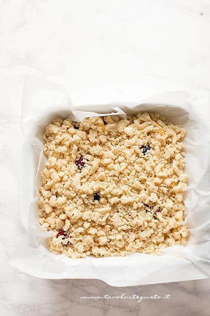 Riempire la superficie della torta con il crumble - Ricetta Torta Crumble alla frutta (pesche e mirtilli)