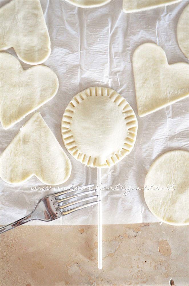 Sigillare i bordi dei lecca lecca con i rebbi di una forchetta - Ricetta Lecca lecca salati di pasta sfoglia