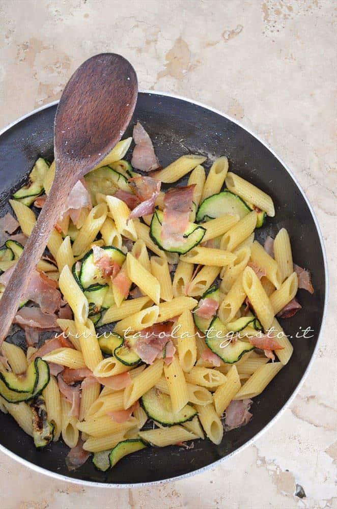 Condire la pasta e aggiungere il grana - Ricetta Pasta al forno con zucchine e speck