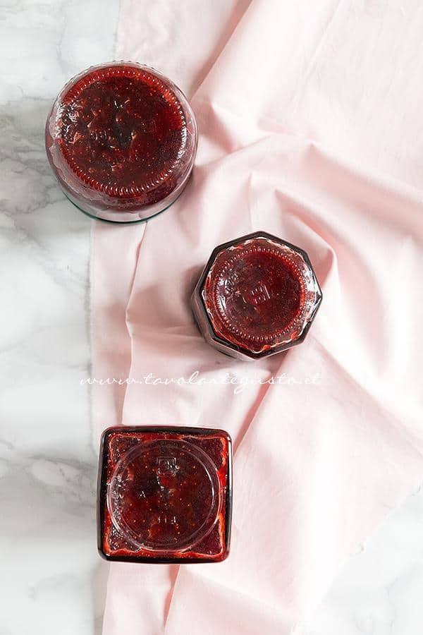 Vasetti pieni di marmellata di fragole in fase di sottovuoto -  Ricetta Marmellata di fragole