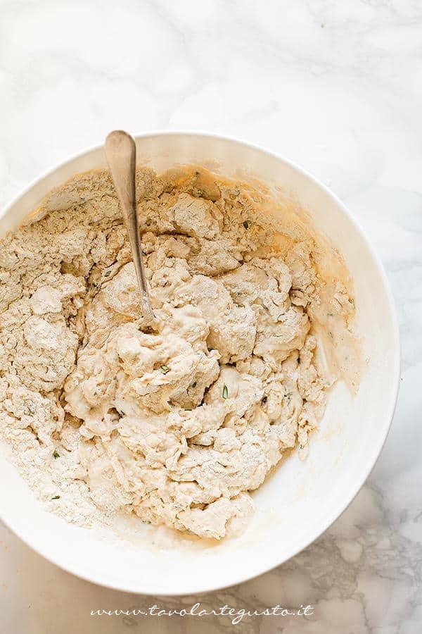 Aggiungere l'accqua e mescolare con un cucchiaio - Ricetta Focaccia di farro