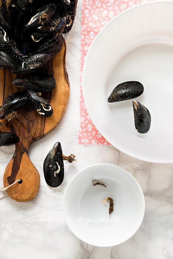Eliminare la barbetta dal mollusco ancora chiuso -  Ricetta Come pulire le cozze