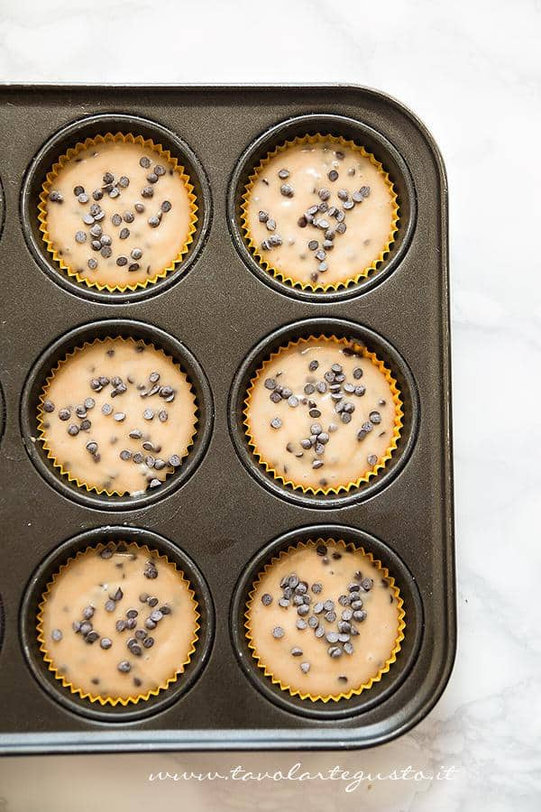 Versare l'impasto nei pirottini - Ricetta originale Muffin con gocce di cioccolato
