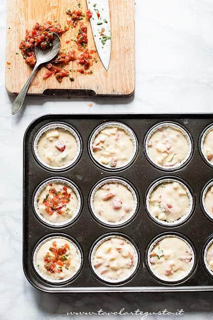 Distribuire l'impasto nei pirottini e condire con pomodorini -  Ricetta Muffin salati provola e pomodorini