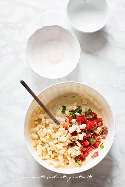 Unire la farcia all'impasto -  Ricetta Muffin salati provola e pomodorini