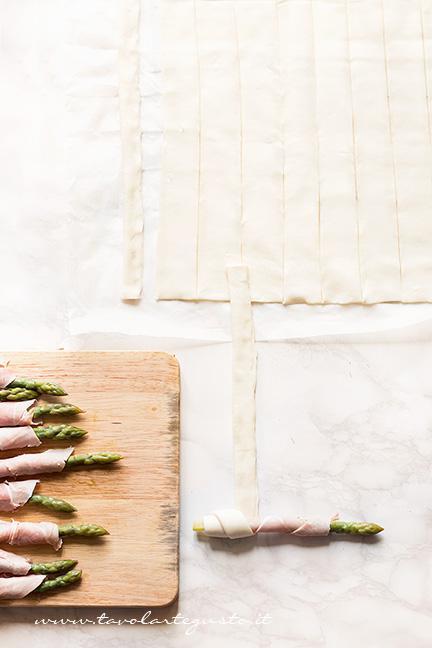 Arrotolare ogni asparago in un cordone di pasta sfoglia - Ricetta Asparagi in crosta di pasta sfoglia
