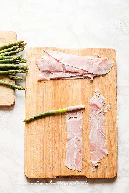 Arrotolare ogni asparago nella fetta di prosciutto1 - Ricetta Asparagi in crosta di pasta sfoglia