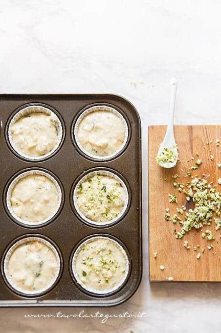 Inserire l'impasto nei pirottini -Muffin alle zucchine