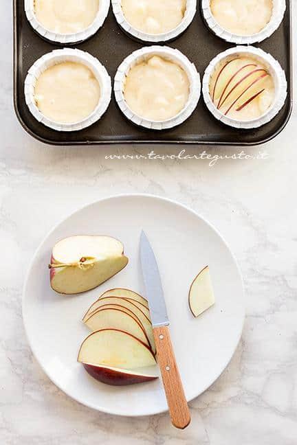 Distribuire l'impasto nei pirottini e tagliare sottili le fettine di mela - Ricetta Muffin alle Mele