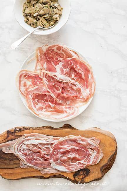Aggiungere le fettine di pancetta sulla carne - Ricetta Involtini di carne con funghi