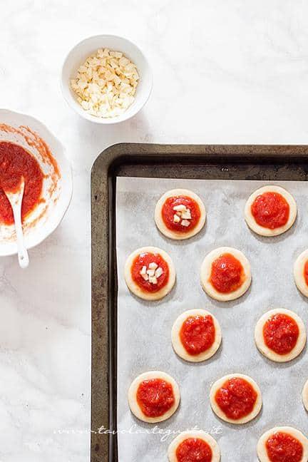 Condire le pizzette con pomodoro e scamorza - Ricetta Pizzette Ragno per Halloween