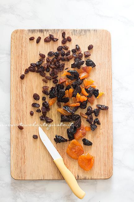 Tagliare a pezzetti la frutta secca - Ricetta Barrette di riso soffiato e cioccolato