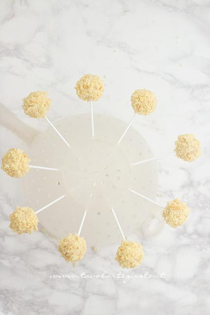 Fare asciugare i cake pops mimosa su una colapasta - Ricetta Cake pops Mimosa