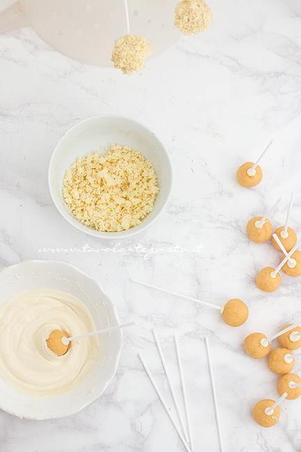 Tuffare le palline nel cioccolato bianco - Ricetta Cake pops Mimosa