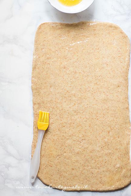 Stendere metà impasto e pennellarlo di burro fuso - Ricetta Cornetti Integrali al miele