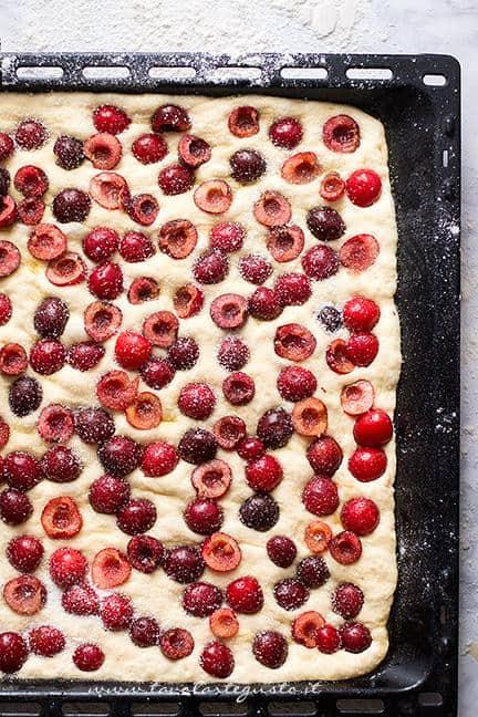 Affondare le ciliegie sulla superficie della focaccia e cospargere di zucchero - Ricetta Focaccia dolce alle Ciliegie