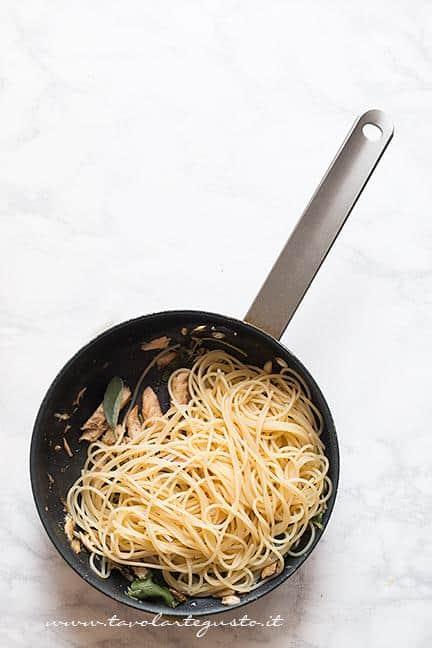 Saltare gli spaghetti nel sughetto allo sgombro - Ricetta Pasta con lo Sgombro