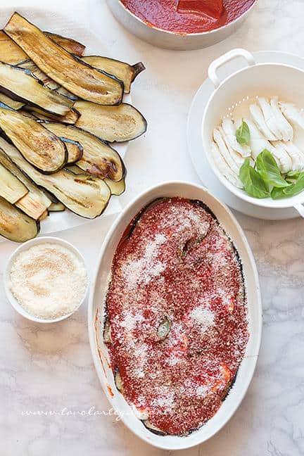 Aggiungere uno strato di salsa e parmigiano - Ricetta Parmigiana di Melanzane