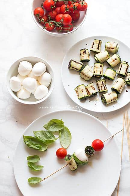 Realizzare gli spiedini con le zucchine, mozzarelline e pomodorini - Ricetta Spiedini di Zucchine