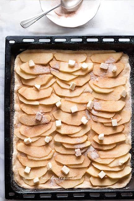 Condire le mele con lo zucchero cannella e fiocchetti di burro Ricetta Pizza con le mele