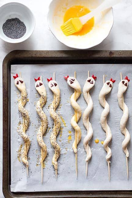 Pennellare i serpenti di pizza e spolverare con semi di papavero - Ricetta Serpenti di pizza per Halloween