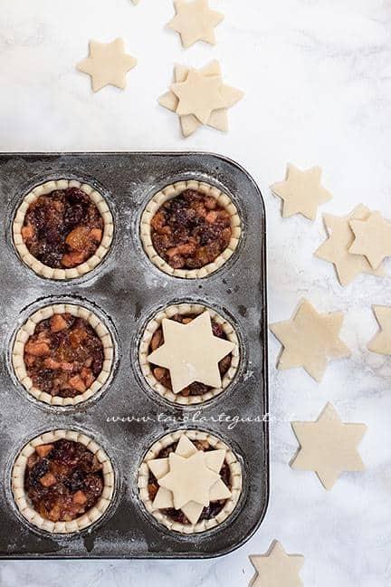 Chiudere la superficie dei mince pie con biscottini a forma di stella in superficie - Ricetta Mince Pies