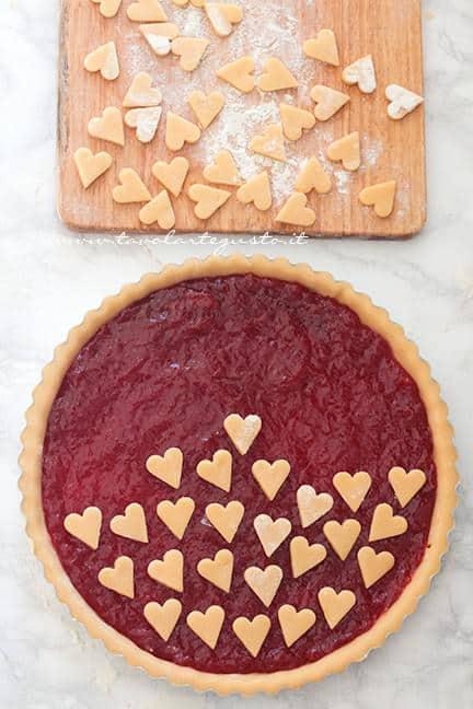 Aggiungere i cuoricini di pasta frolla sulla crostata - Ricetta Crostata con cuori per San Valentino
