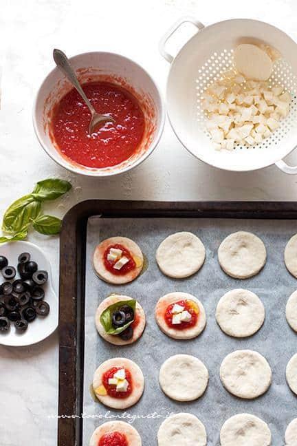 Condire le pizzette con sugo, mozzarella oppure olive - Ricetta Pizzette allo yogurt