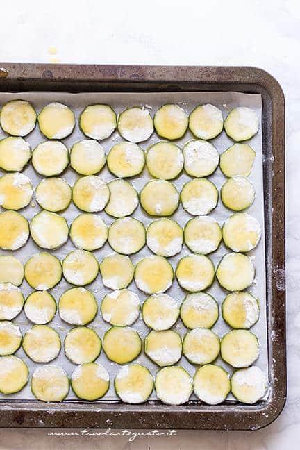 Condire le patatine di zucchine con un filo d'olio e cuocere in forno - Ricetta Chips di zucchine