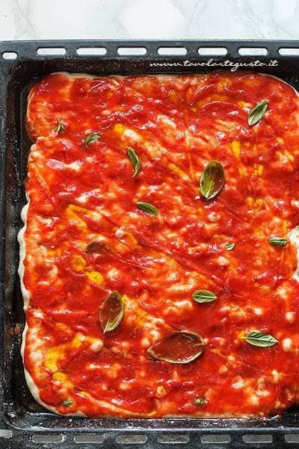 Condire la pizza con pomodori pelati, basilico e olio - Ricetta pizza in teglia